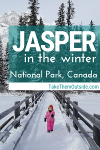 A toddler in a pink snow suit walking across Pyramid Island Bridge in Jasper National Park