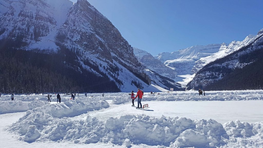 people walking and skating on a frozen Lake Louise on a beautiful sunny winter day