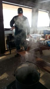 A Jasper National Park Interpreter making hot chocolate over the wood stove
