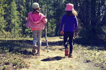 two girls hiking on a wooded trail one carrying a large stick