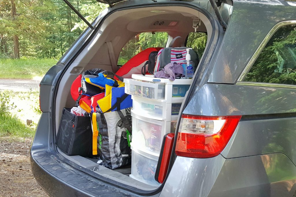 a van trunk open to show family camping gear all packed and organized in bags and tubs