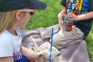 two kids having a slushy treat outside on a picnic blanket