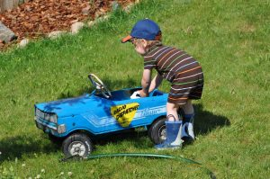 A little boy having fun with outdoor toys washing his play car with the water hose