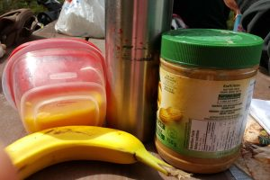Making easy picnic foods with a banana, peanut butter, wraps on a picnic table
