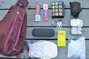 all the items found in a mom purse, diaper, sunglasses, keys, emergency kit, shopping bag, wallet, snacks, baby wipes.