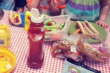 a picnic table covered in a red checkered table cloth and picnic foods