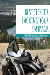 an open daypack sitting on some rocks overlooking a river and town, text reads best tips for packing your daypack