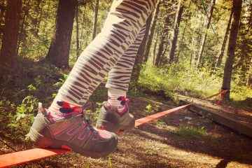 child's feet walking on a tight rope / slackline