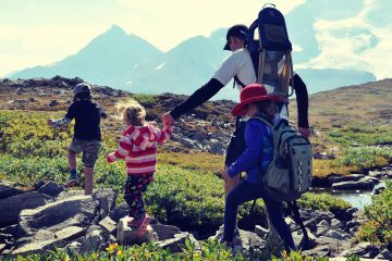 A dad and 3 kids on a family hike in the mountain alpine of Jasper National Park, Canada