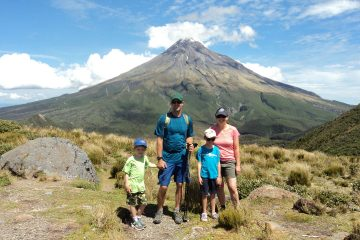 Connect your family to nature: Man, woman, and two children standing together with Mt. Taranaki of New Zealand in the background. text reads making nature connections, one family's story