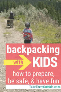 A family hiking with backpacks on an open meadow trail