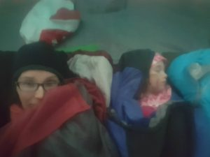 a selfie of a mom and toddler all bundled up in sleeping bags in a tent