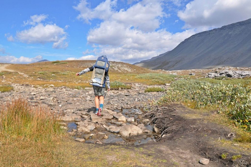 a boy with a backpack crossing a rocky creek