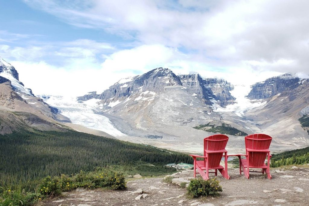 2 red parks canada chairs overlooking athabasca glacier and the icefields parkway