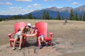 a mom and daughter sitting in two red Adirondack chairs while on a hike in Jasper National Park