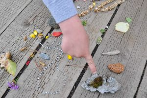 A child's finger pointing to nature scavenger hunt treasures like rocks, leaves, twigs, and flower petals