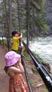 two kids using cameras to photograph a rushing river