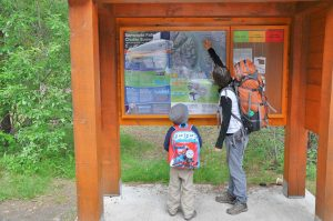 Mom wearing a backpacker's pack is pointing the trail out on a map to her small child, also wearing a small backpack