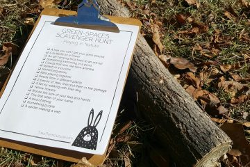 a clipboard holding a nature scavenger hunt sitting on the ground against a log