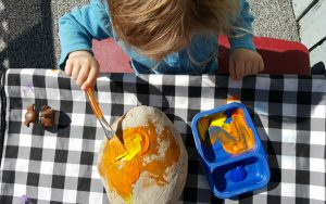 toddler painting a large rock with orange paint as part of the summer planner activities