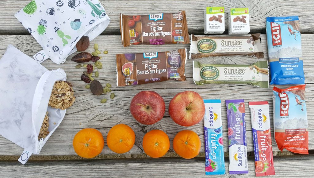 various snack foods like granola bars, fruit, nuts, and dried fruit on a picnic table
