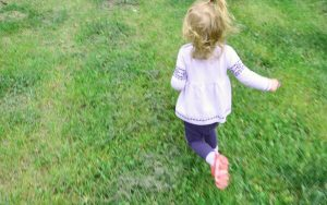 Toddler wearing a white sweater running on the grass
