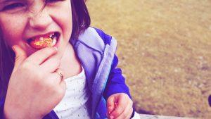 a girl biting into an orange