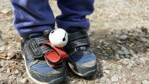 toddler's blue running shoes with a bear bell attached to them