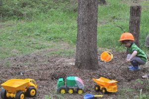 Little boy wearing a play hard hat playing with toy trucks and tractors outside in the dirt