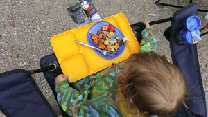 Looking down on a toddler eating food off a yellow lap tray, while sitting in a folding chair at a campsite