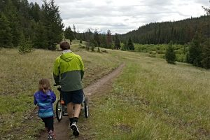 A family out for a walk in an open meadow at Valley of the Five Lakes