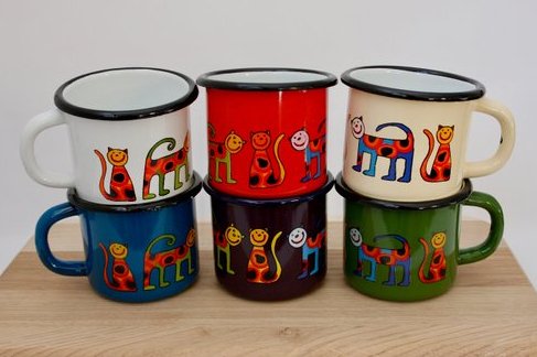 Various colours of enamel camping mugs with cute cat drawings on them
