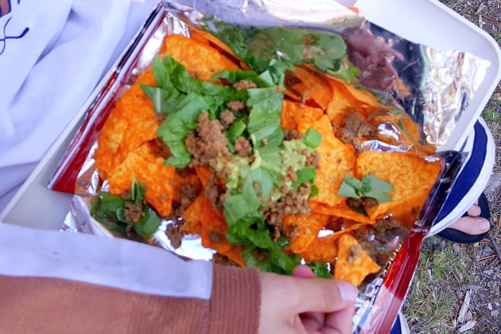 shredded lettuce, taco meat, and guacamole on top of an open bag of Doritos
