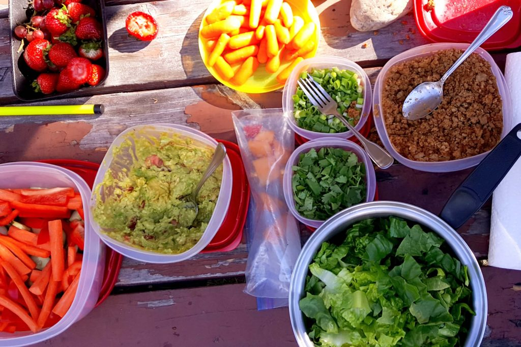 individual containers of taco in a bag toppings: guacamole, lettuce, ground meat, green onions