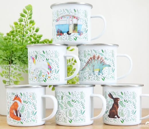 Woodland themed enamel mugs stacked on a tabletop.
