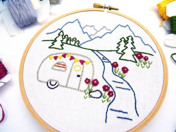 a handmade embroidery of a vintage camper in the mountains