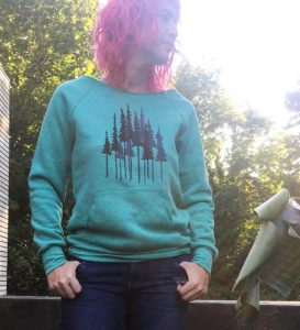 A woman wearing a teal sweatshirt with a forest print.