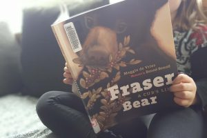 a young girl reading Fraser Bear on the couch