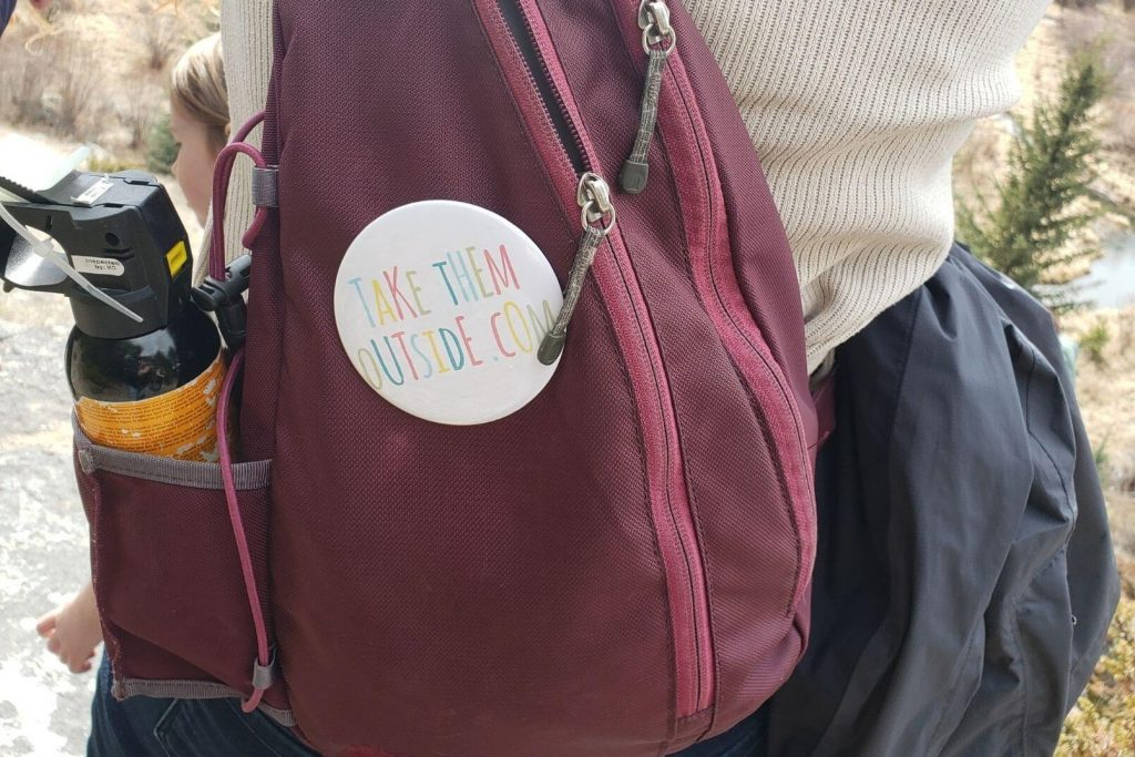 a shoulder bag with a take them outside pin and bear spray in the pocket