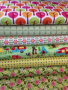 bolts of colorful fabric with a woodland camping theme