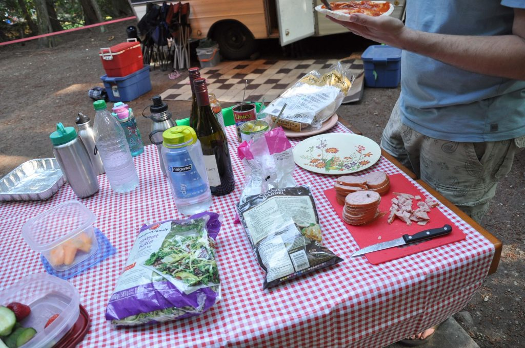 A campground picnic table covered with food supplies to make pita pizzas for dinner