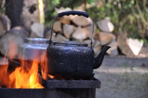 boiling water over a campfire with camp kettles