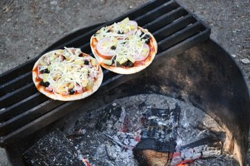 two pita pizzas roasting on the grill over the campfire
