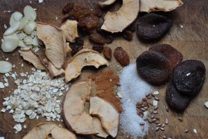 dried apples, dried fruit, oats, sugar - ingredients for instant oatmeal - spread out on a wooden cutting board
