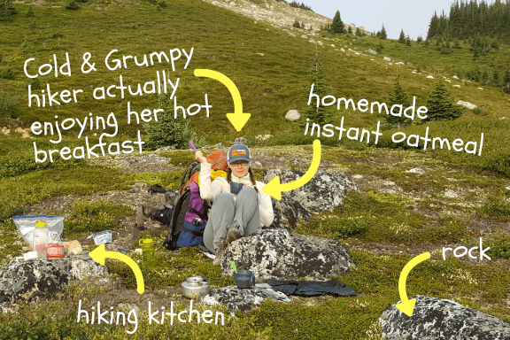 A woman sitting on the ground eating oatmeal. Text written on the photo points to various things in the photo like her, her oatmeal, and the hiking kitchen