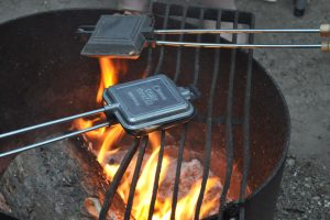 Two pie irons held over a campfire