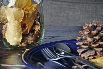 a blue plate with cutlery and a pinecone sitting on top