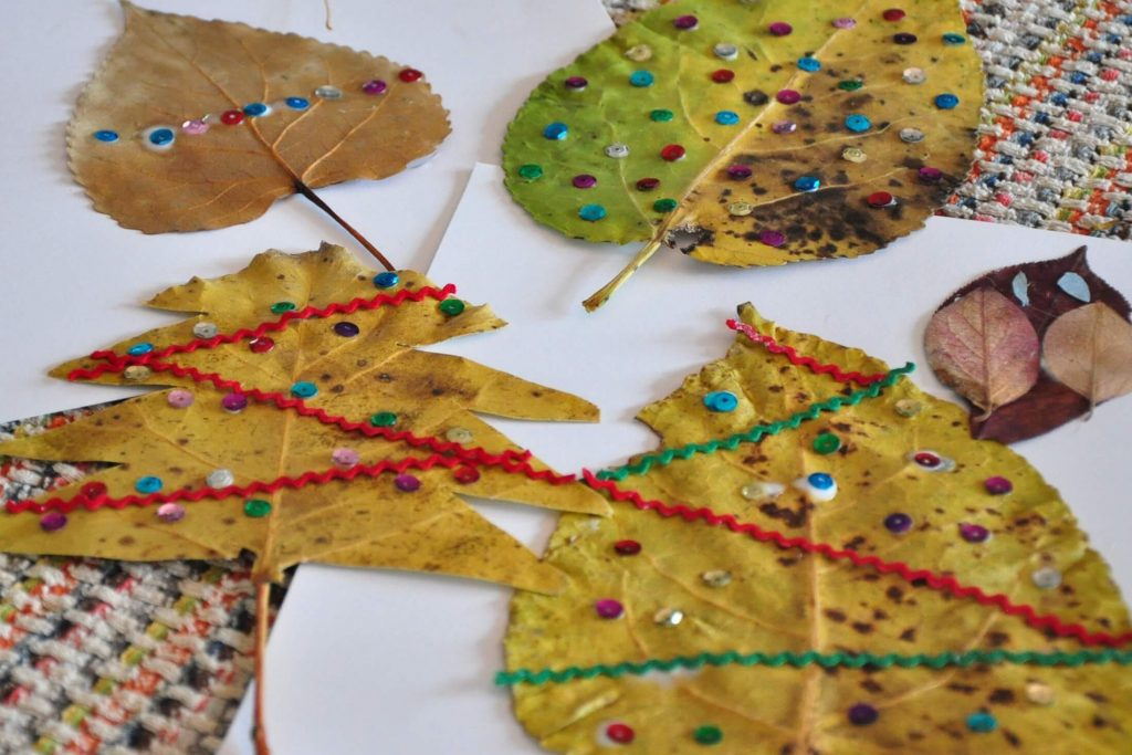 Various dried leaves decorated with sequins and ric rack to look like miniature Christmas Trees