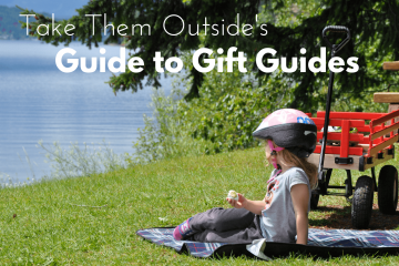 little girl sitting on a picnic blanket beside her red wagon, text overlay reads Take Them Outside's Guide to Gift Guides