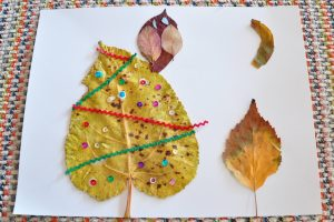 A kid's leaf art project. It's an owl sitting on a tree with the moon overhead